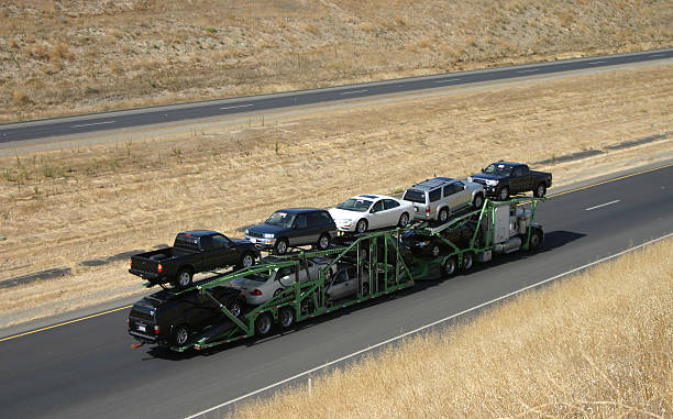 Car Carrier A large truck delivers new cars via highway. carrying stock pictures, royalty-free photos & images