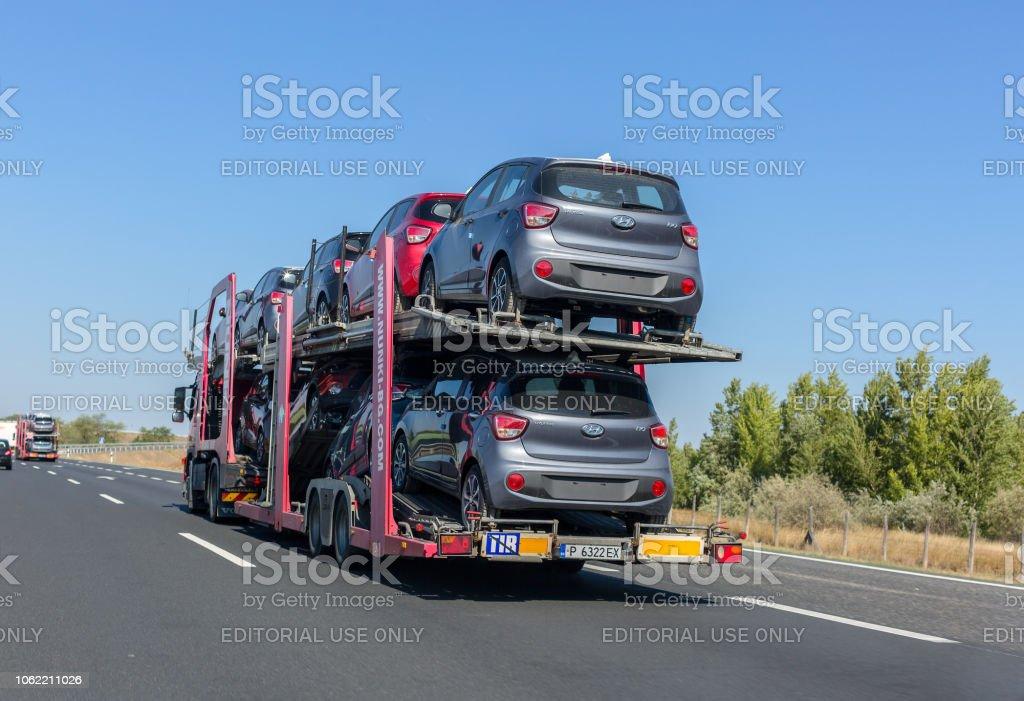Car carrier trailer with Hyundai cars on bunk platform. Car transport...