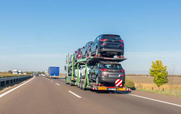 autoanhänger träger mit neuen autos zum verkauf auf koje-plattform auf der autobahn - autotransporter stock-fotos und bilder