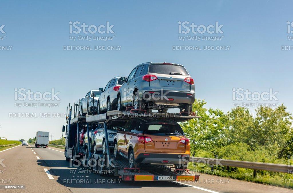 Car carrier trailer with new Suzuki Vitara cars on bunk platform. Car...