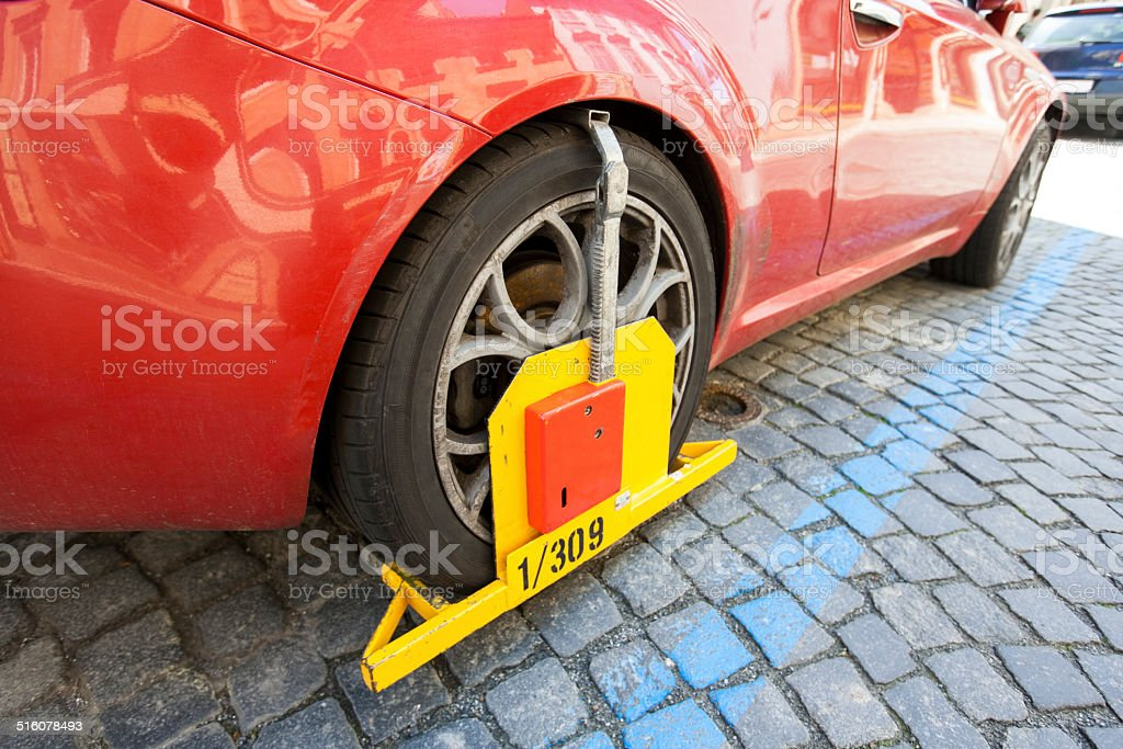 Car clamped on cobbled street stock photo