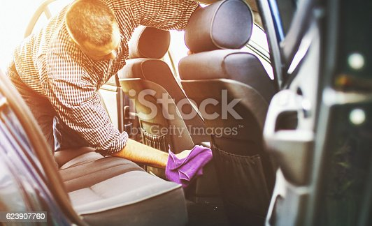 Closeup of partially unrecognizable man cleaning rear seats of his car. He's using soft purple cloth to finish the celaning. Back lit with flaring sunlight from the background.