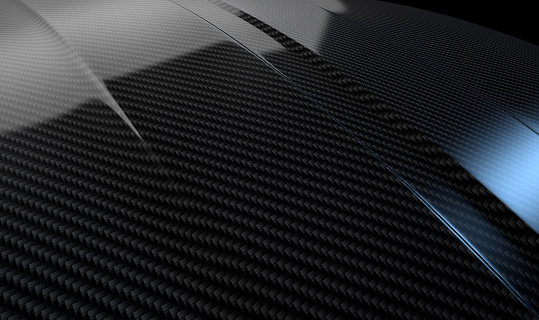 An abstract section of the contours of a carbon fibre automobile bonnet with dramatic lighting on a dark studio background
