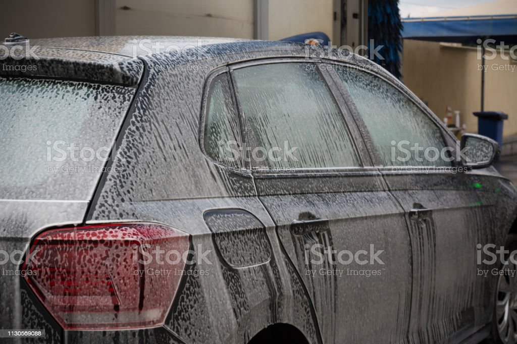 Car Covered by Active Foam During Car Washing entering the Brushes of...