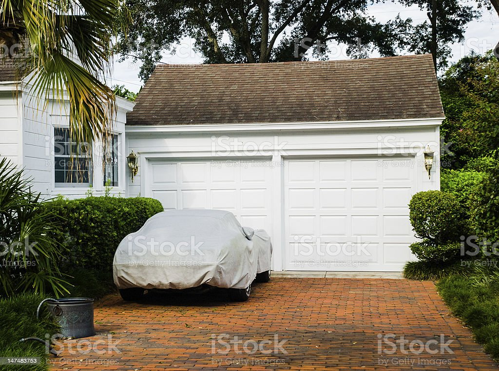 Car Covered on Brick Driveway with White Two Car Garage stock photo