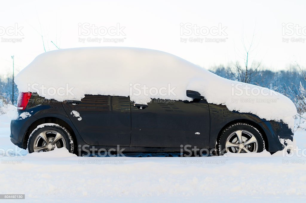 Car covered with snow in the winter. stock photo