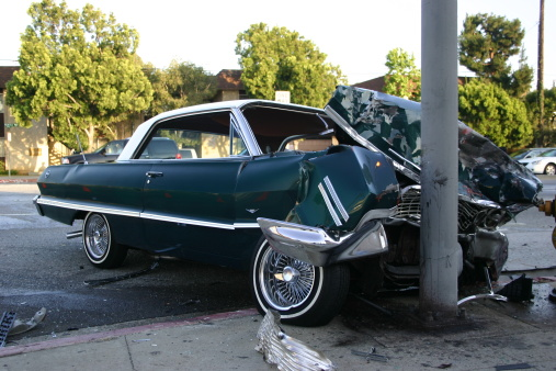 vintage car smashed up onto the curb