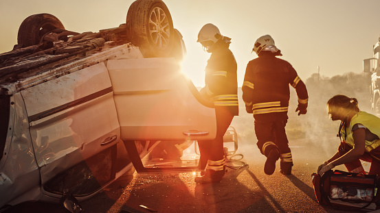 Car Crash Traffic Accident: Paramedics and Firefighters Plan Rescuing Passengers Trapped in Rollover Vehicle. Medics Prepare Stretchers and First Aid Equipment. Firemen Use Hydraulic Cutters Spreader