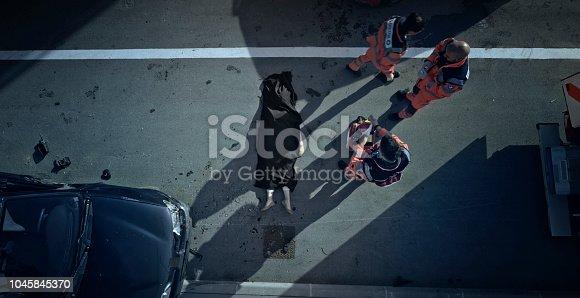 istock Car crash victim covered with black sheet and paramedic team walking away 1045845370