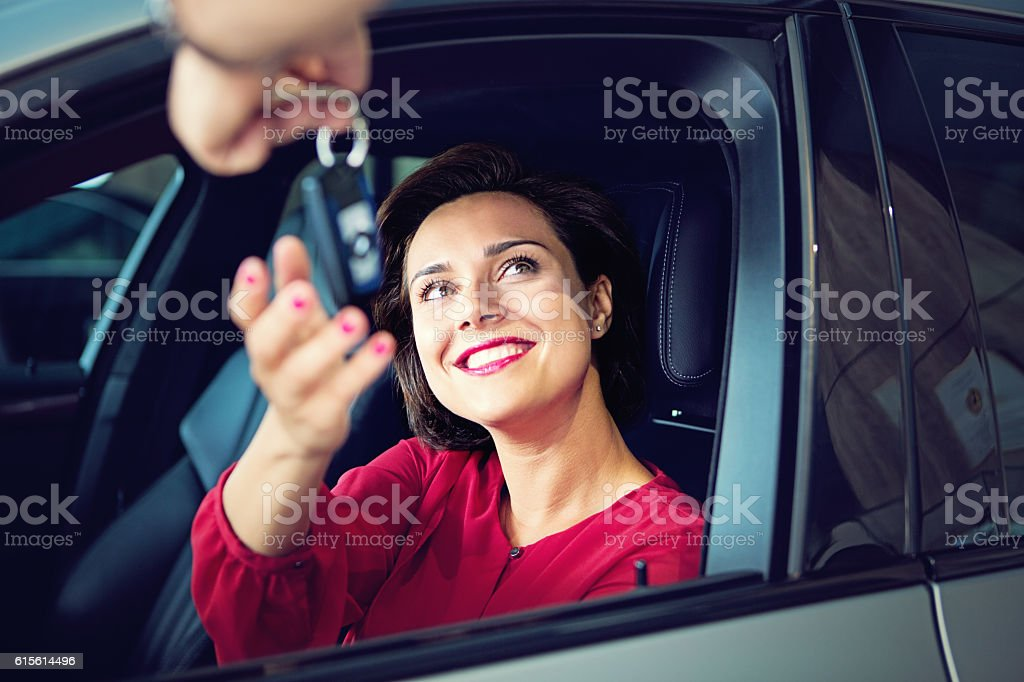 Car dealer gives car keys to the businesswoman stock photo