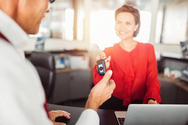 car dealer giving car keys to the client - mietwagen stock-fotos und bilder