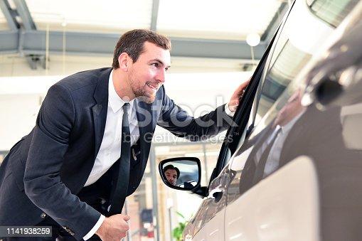 1049198210 istock photo Car dealer in showroom present new car for customer 1141938259