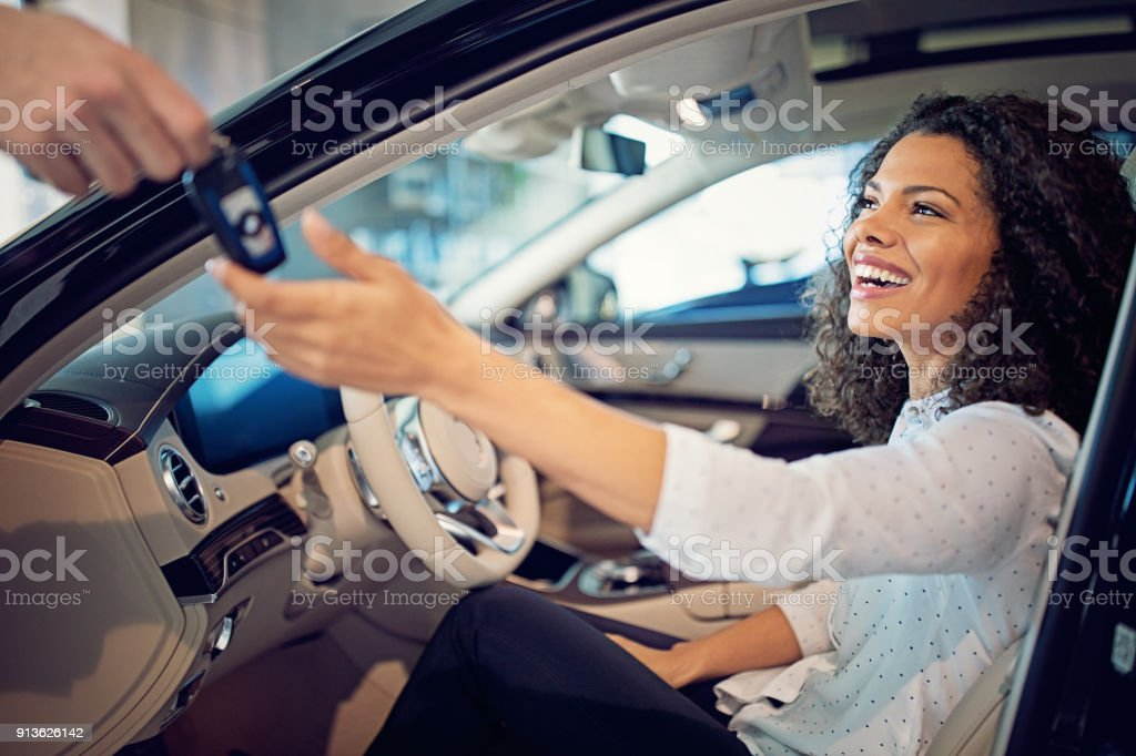 Car dealer is giving key for a new car to a businesswoman stock photo