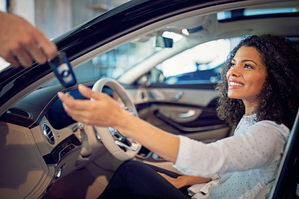 Car dealer is giving key for a new car to a businesswoman Car dealer is giving key for a new car to a businesswoman car key stock pictures, royalty-free photos & images
