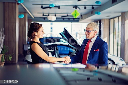 136591825istockphoto Car dealer is shaking hand with a customer after successful deal 1019597200