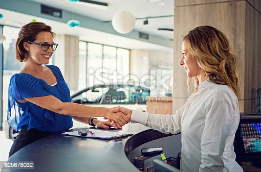 istock Car dealer is shaking hand with a customer after successful deal 825678032