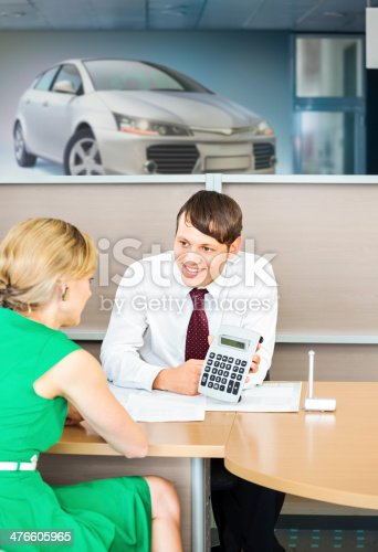 136591825istockphoto Car dealer making an offer, showing price. 476605965