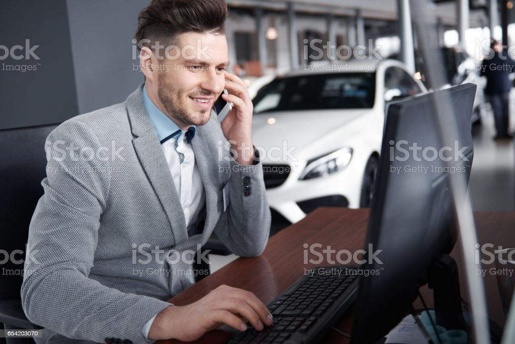 Car dealer on the phone talking with client stock photo
