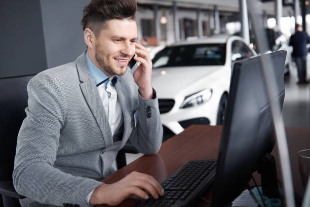 Car dealer on the phone talking with client Car dealer on the phone talking with client car salesperson stock pictures, royalty-free photos & images