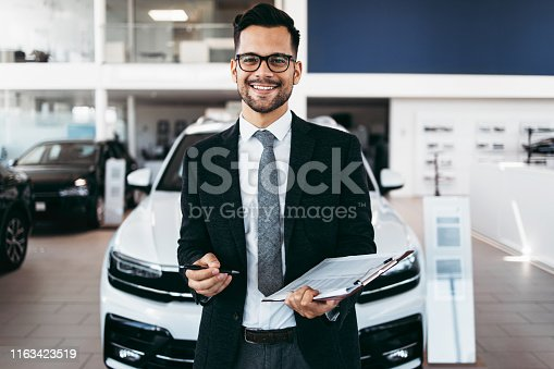 Good looking, cheerful and friendly salesman poses in a car salon or showroom and looks at camera.