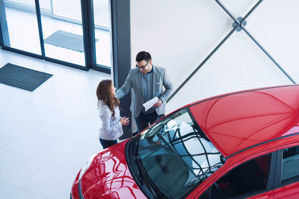 Car dealership. Car dealer presenting perfect city car for an attractive businesswoman. happy people buying new vehicle automobile. car salesperson stock pictures, royalty-free photos & images