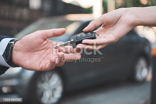 istock Car dealership.Young man receiving car key from saleswoman. 1053485392