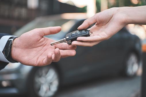 istock Car dealership.Young man receiving car key from saleswoman. 1053485392