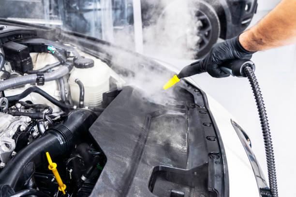 Auto-Details. Autowaschmaschine. Reinigung Auto mit heißem Dampf. Heißes Steam-Motorwaschen. Sanfte Beleuchtung. Autowaschanlage Mann Reinigungsfahrzeug. – Foto