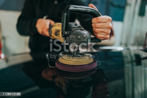 Man using the machine to polish the car hood, close-up on his hands.