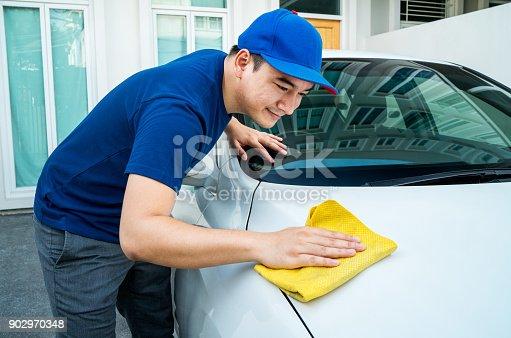 Car detailing, Man in blue uniform clean a white car in hand holding a microfiber washing large car