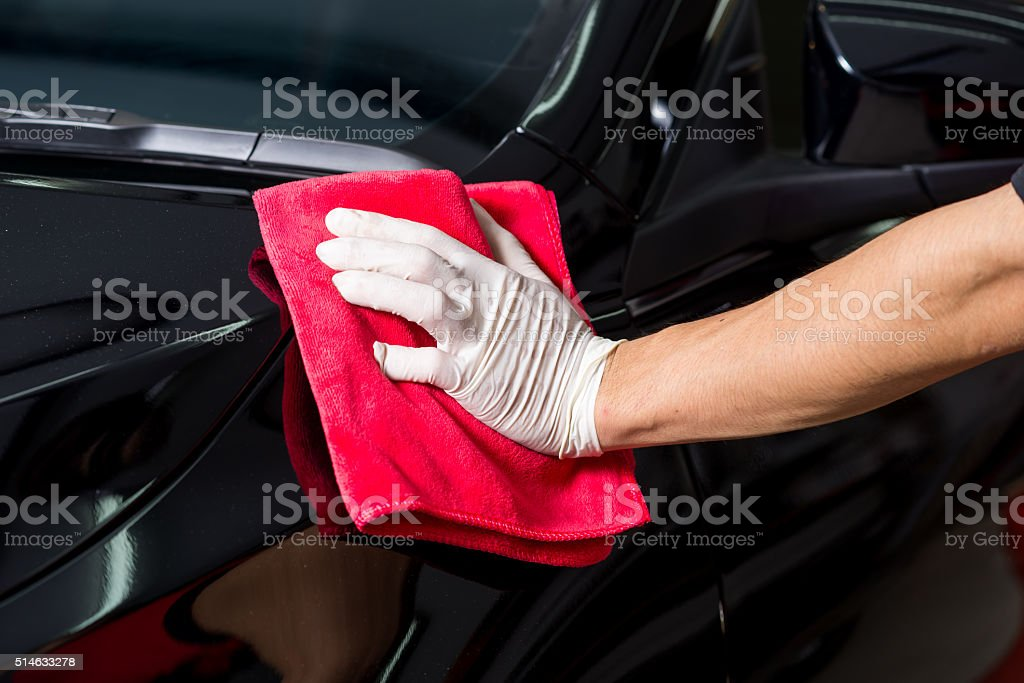Car detailing series : Worker cleaning black car stock photo