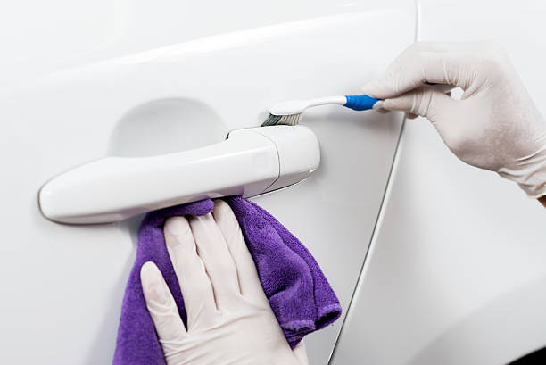 Car detailing series : Worker cleaning white car stock photo