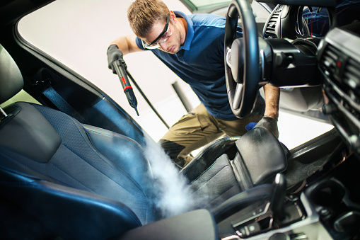 Closeup side view of a young man using fine brush and cleaning AC vents during car interior detailed cleaning.