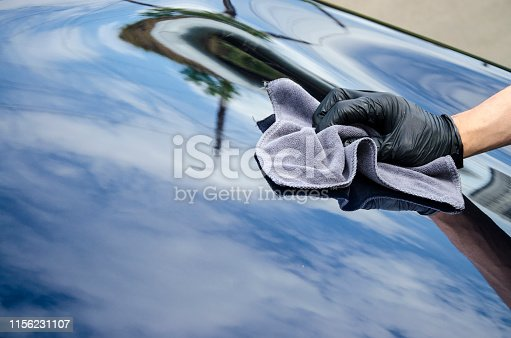 Car detailing - the man holds the microfiber in hand and polishes the car. Hand wipe down paint surface of shiny black crossover after polishing and ceramic coating.