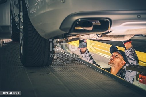 Car Diagnostic Technician Under the Vehicle. Automotive Industry.