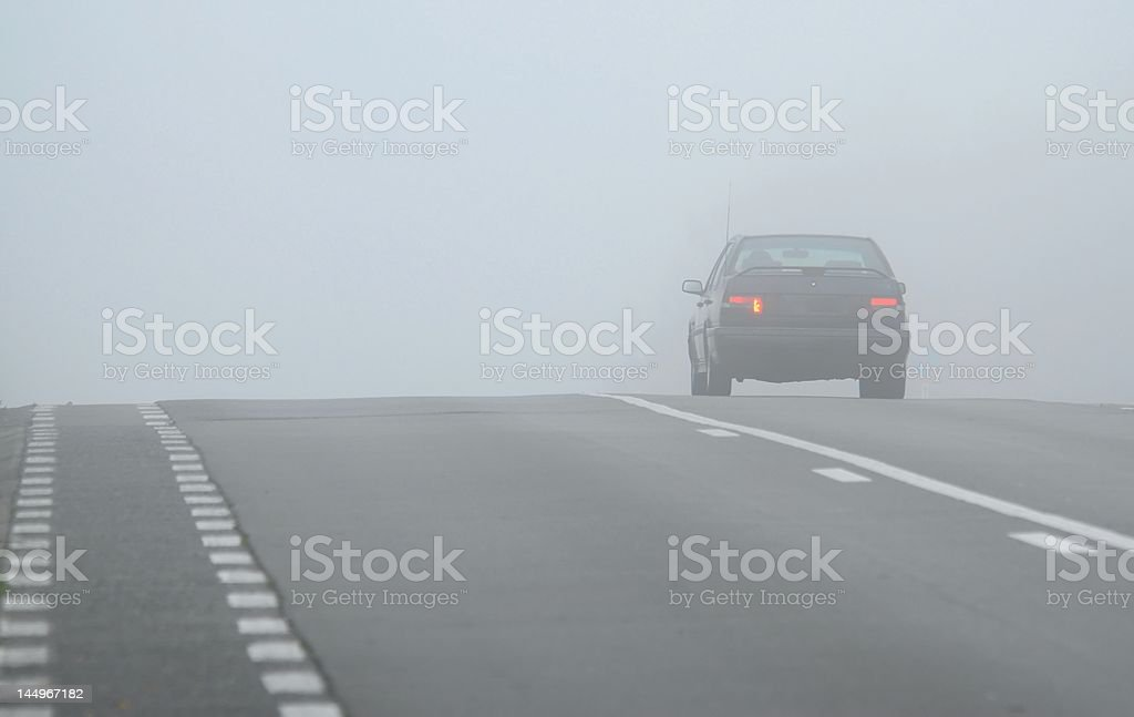 Car disappearing through fog royalty-free stock photo