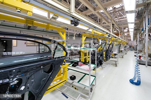 1069360792 istock photo car door on conveyor. Robotic equipment makes Assembly of car. Modern car Assembly at factory 1076327334