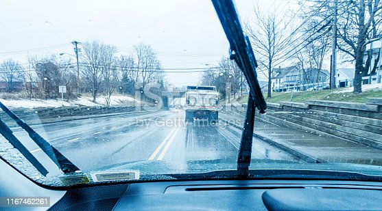 Car driver point of view personal perspective looking through the windshield while following a large snow plow dump truck which is spraying road salt on the slippery downhill road ahead as it approaches a railway bridge underpass during a sloppy rain and icy sleet storm in early February near Rochester, New York State. The windshield wipers are working hard to clear the frozen water drops constantly smacking and spattering on the glass. Part of a