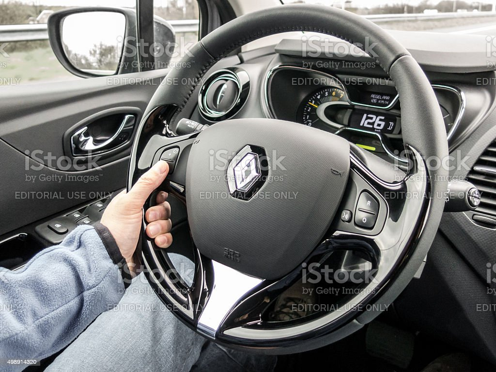 Car driver hand on the wheel on cruise control driving stock photo