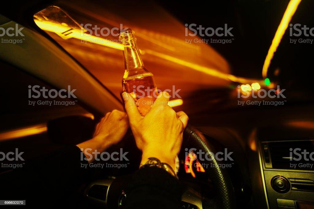 Pilote automobile détient une boissons alcooliques pendant que vous conduisez la nuit - Photo