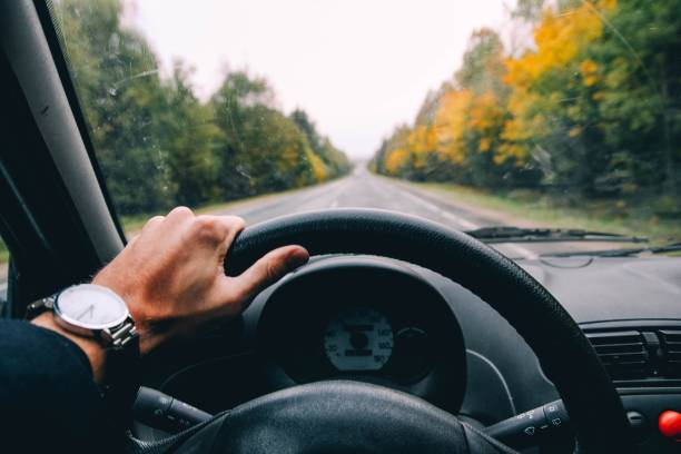 conductor del coche sostiene la rueda en un día soleado. - conducir fotografías e imágenes de stock