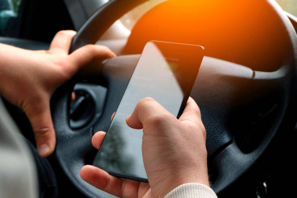 car driver looks at smartphone while driving the car - detraction stock pictures, royalty-free photos & images