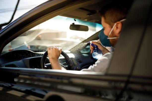 Car driver sanitizing steering wheel stock photo