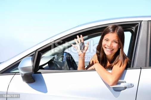 Asian car driver xwoman smiling showing new car keys and car. Mixed-race Asian and Caucasian girl.