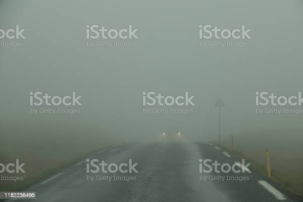 Photo of Car drives through the thick white fog down an empty country road in Scandinavia