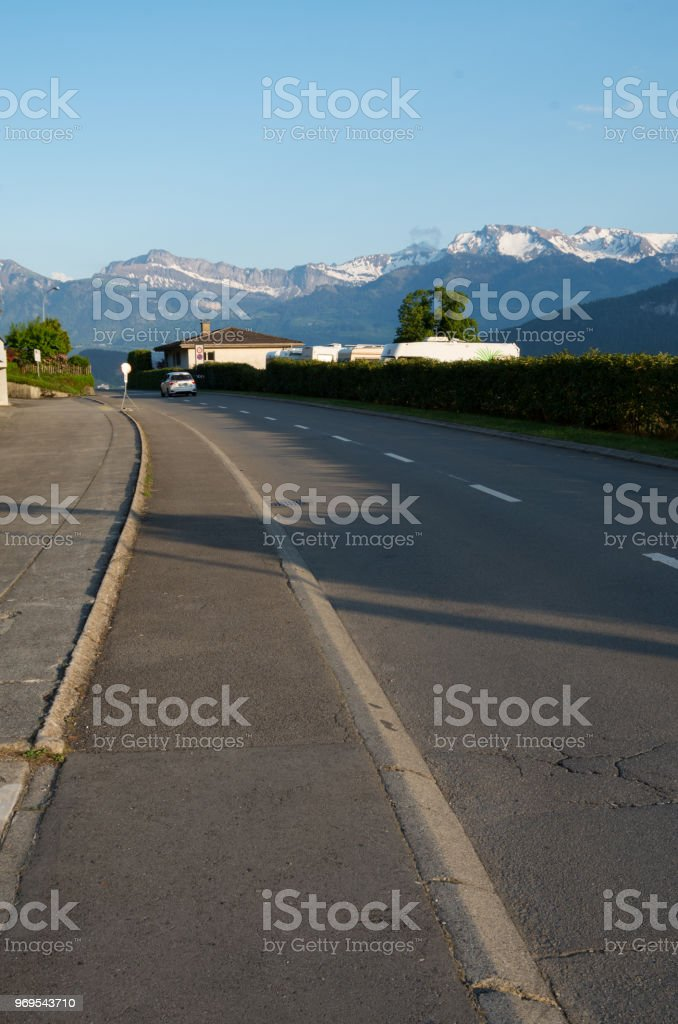 car driving away down alpine road stock photo more pictures of