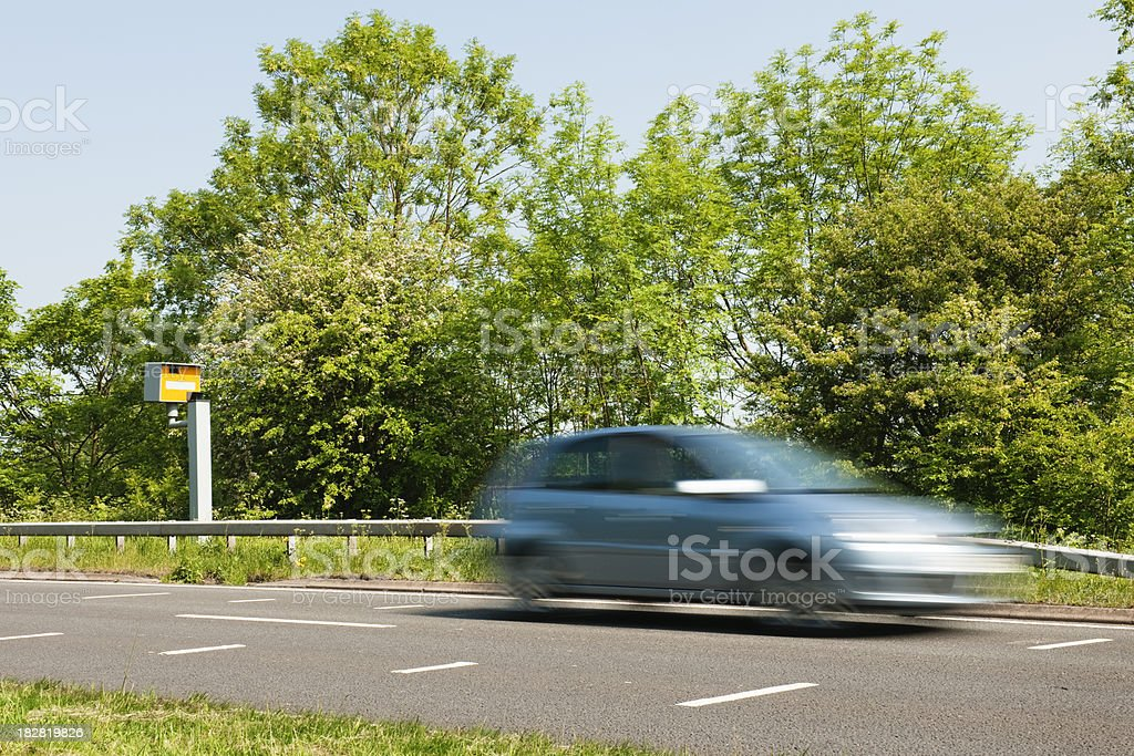 Car driving fast past speed camera stock photo