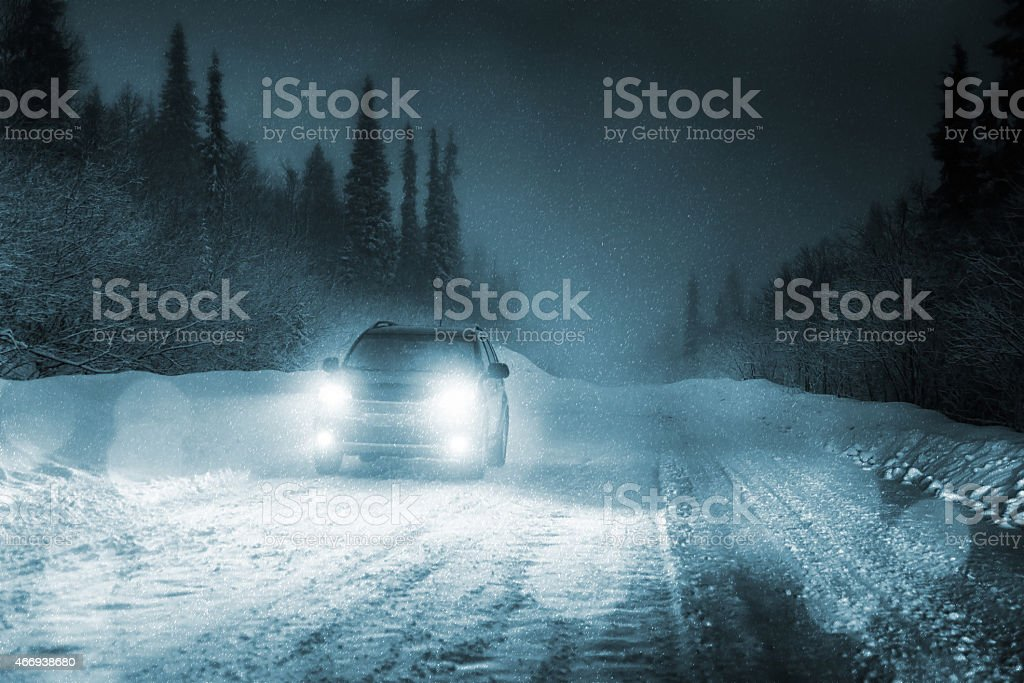 Car driving in forest with headlights lighting snowy road stock photo