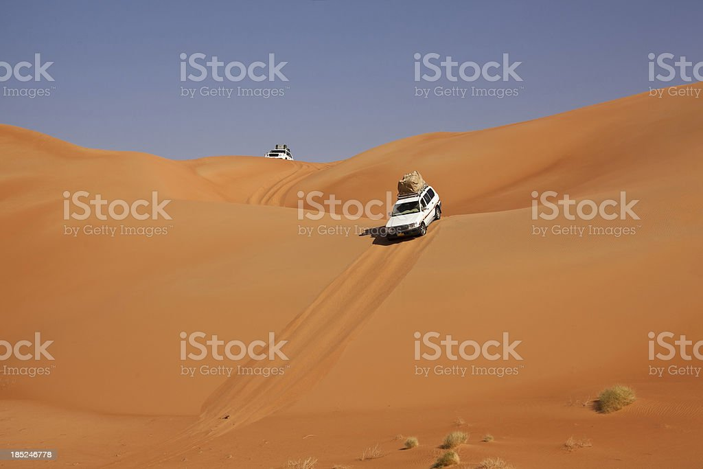 Car driving in the desert between sand dunes stock photo