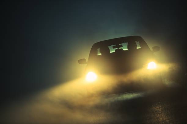 Car Driving in the Fog Car Driving in Dense Fog. Dangerous Road Conditions. Night Time Driving in Fog. headlight stock pictures, royalty-free photos & images